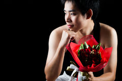 Asian boy with red bouquet in dark background Royalty Free Stock Photography