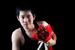 Asian boy with red bouquet in dark background Royalty Free Stock Photos