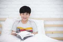 Asian boy rest on the bed and reading book. At home . with smile face and looking camera Stock Image