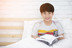 Asian boy rest on the bed and reading book Royalty Free Stock Photos