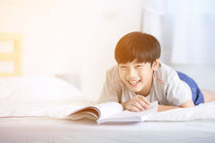 Asian boy rest on the bed and reading book with smile face Stock Photography