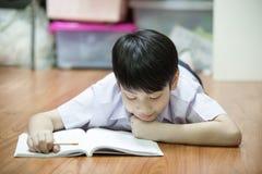 Asian boy rest on the floor doing homework Stock Photos