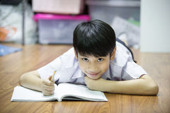 Asian boy rest on the floor doing homework Royalty Free Stock Photography