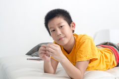 Asian boy resting comfortably on his bed Royalty Free Stock Image