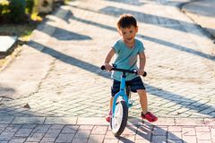 Asian boy ride balance bicycle in park. Handsome healthy Asian boy, 3 years old, riding balance bike by both feet in evening with sunset light. training bicycle royalty free stock photos
