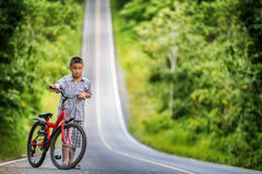 Asian boy riding on his bycicle Royalty Free Stock Images