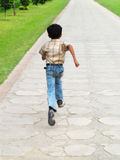 Asian boy running. Little Asian boy running away on a path outdoors Royalty Free Stock Images