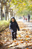 Asian boy running on the road with yellow leaves Stock Photos