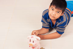 Asian boy saving money in piggybank Royalty Free Stock Photos