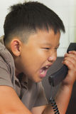 Asian boy scold at the telephone. Young asian boy scold at the telephone Stock Photography