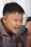 Asian boy scold at the telephone. Young asian boy scold at the telephone Stock Photos