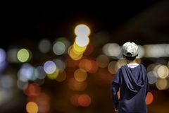 Asian boy see blurred lights of the house and street light, brig royalty free stock photo