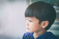 Asian Boy seriously looking out of window Royalty Free Stock Image