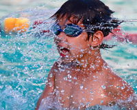 Asian  boy shakes water from his head. While in an outdoor swimming pool Royalty Free Stock Photos