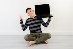 Asian boy showing blank laptop at home. Copyspace for mock up and text Stock Photo