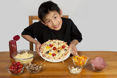 Asian boy showing off home-made pizza Royalty Free Stock Photo