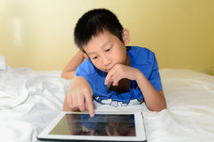 Asian boy siblings on bed playing tablet. Stock Images
