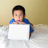 Asian boy siblings on bed playing tablet. Royalty Free Stock Photography