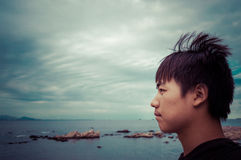 Asian boy side face profile. By the sea Royalty Free Stock Photography