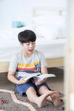 Asian boy sit on the floor and reading book with smile face at h Stock Photos