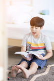 Asian boy sit on the floor and reading book with smile face at h Royalty Free Stock Photography