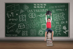 Asian boy sit on pile of books in class Royalty Free Stock Images