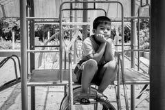 Asian boy sitting alone at playground. Black and white tone Stock Photo