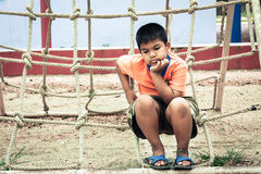 Asian boy sitting alone at playground Royalty Free Stock Photos