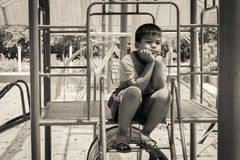 Asian boy sitting alone at playground Royalty Free Stock Photo