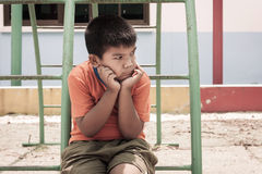 Asian boy sitting alone at playground. Vintage tone Stock Images