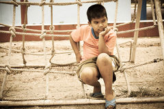Asian boy sitting alone at playground. Vintage tone Royalty Free Stock Images
