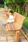 Asian boy sitting on the bench Royalty Free Stock Images