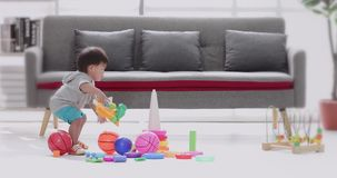 Asian boy sitting on floor and playing toys. stock footage