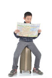 Asian boy sitting on lugguage and holding map on white Stock Images