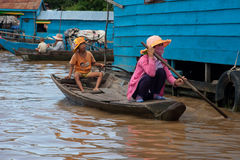 Asian boy sitting with mother in the boat on the river near thei Royalty Free Stock Photo