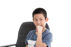 Asian boy sitting on office chair and thinking Royalty Free Stock Photo