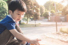 Asian Boy is sitting in a Park. Copy space Stock Image