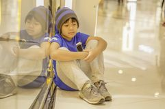 Asian boy sitting sad and stressed In the mall, the concept of losing children from parents royalty free stock photography