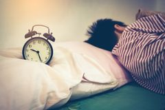 Asian boy sleeping on bed., antique black alarm clock near by. V Stock Photos