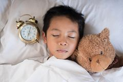 Asian boy sleeping on bed white pillow and sheet with alarm clock and teddy bear Royalty Free Stock Photos