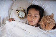 Asian boy sleeping on bed white pillow and sheet with alarm clock and teddy bear Royalty Free Stock Photo