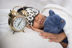 Asian boy sleeping on bed white pillow and sheet with alarm clock and teddy bear Stock Photo