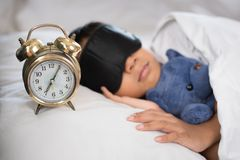 Asian boy sleeping on bed white pillow and sheet with alarm clock and teddy bear. Boy sleeping in morning wearing sleep mask Royalty Free Stock Images