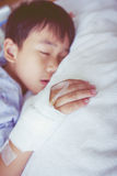 Asian boy sleeping on sickbed, saline intravenous (IV) on hand. Royalty Free Stock Photography