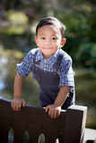 Asian boy smiling and looking straight into camera while outdoors Royalty Free Stock Photography