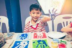 Asian boy smiling and showing hands in paint. Pop art style. Handsome asian boy smiling and showing hands in paint. Pop art style, imprint of a kids hand on art stock photos