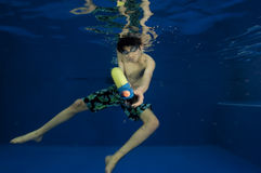 Asian boy with squirt gun under water Stock Image