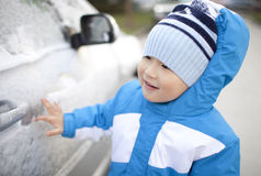 Asian boy standing beside the car with snnow Royalty Free Stock Images