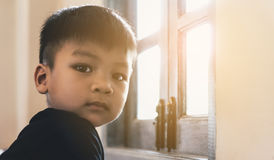 Asian boy standing at a sun light bright window. For hope Royalty Free Stock Photos