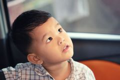 Asian Boy Starting With Suspicion In A Car Stock Photography